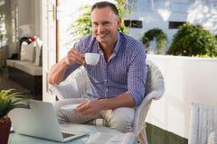 成熟商人饮用的咖啡,当坐由在室外咖啡馆时的膝上型计算机 库存图片