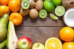 成熟在一个圈子的果子梨猕猴桃石灰椰子苹果橙色普通话谎言在一张木桌上在地方的中心为 库存照片
