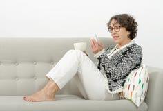 成熟在沙发的妇女饮用的茶 免版税库存照片