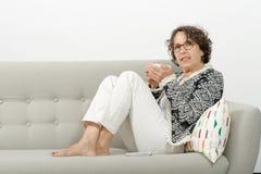 成熟在沙发的妇女饮用的茶 图库摄影