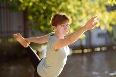 成熟在海滩的女子实践的瑜伽室外锻炼在河附近 图库摄影