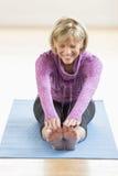成熟在瑜伽席子的妇女感人的脚趾 库存照片
