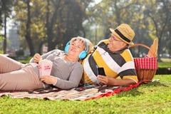 成熟在耳机的夫妇听的音乐在公园 库存照片