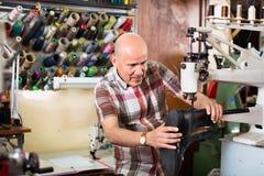 成熟在针车床的工作员缝合的皮靴 免版税库存照片