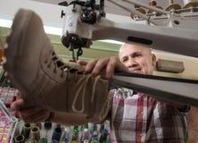 成熟在针车床的工匠缝合的皮靴 免版税库存图片