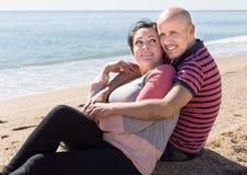 成熟坐在海附近的人和女性 免版税库存图片