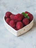 成熟大莓和薄菏小树枝在一个碗的以心脏的形式 免版税库存照片