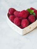 成熟大莓和薄菏小树枝在一个碗的以心脏的形式 免版税库存图片