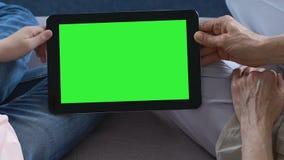 成熟夫人和小孩递拿着有绿色屏幕的,技术片剂 股票视频