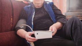成熟夫人检查她的健康状态与手工测压器-措施压力-单独领抚恤金者在家 免版税库存照片