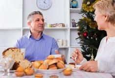 成熟夫妇吃早餐在欢乐圣诞节桌上 图库摄影