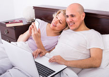 成熟夫妇在与膝上型计算机的床上 图库摄影