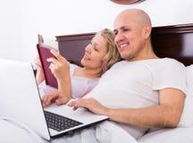 成熟夫妇在与膝上型计算机的床上 库存照片