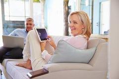 成熟夫妇在家在使用数字式设备的休息室 图库摄影