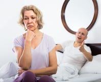 成熟夫妇在床上的整理关系 库存图片
