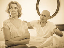 成熟夫妇在床上的整理关系 免版税库存图片