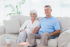 成熟夫妇坐长沙发 图库摄影