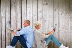 成熟夫妇的综合图象使用膝上型计算机和片剂个人计算机的 免版税库存图片