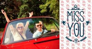成熟夫妇的综合图象在欢呼在照相机的红色敞蓬车的 免版税图库摄影