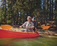 成熟夫妇获得乐趣在有皮船的湖 库存图片