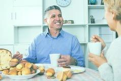 成熟夫妇食用一顿下午快餐用新松饼和cak 库存图片