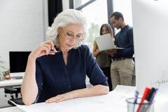 成熟女实业家与文件一起使用,当坐在她的工作场所时 免版税库存图片