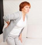 成熟女性有痛苦后面 免版税库存图片
