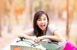 成熟妇女乘驾惊奇自行车和表示  库存照片