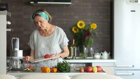成熟妇女切站立在厨房里的蕃茄 他尝试一个片断并且点头满意 素食烹调,母亲` s 影视素材