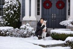 成熟妇女和她的家庭尾随在雪的外部 免版税库存图片