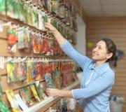成熟妇女在商店选择种子 免版税库存图片