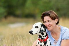 成熟妇女在室外的草甸拥抱一条达尔马希亚狗 免版税库存照片