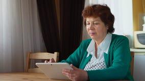 成熟妇女在家使用一张白色片剂个人计算机-侧视图 库存照片