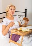 成熟妇女在床上的享用早餐 免版税库存图片