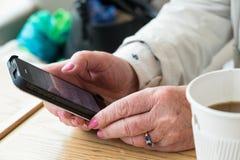 成熟妇女在手上的拿着智能手机 免版税库存图片