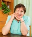 成熟妇女在桌上在家或办公室 免版税库存图片