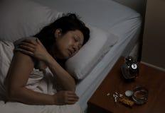 成熟妇女在物理痛苦中,当设法睡觉时 库存图片