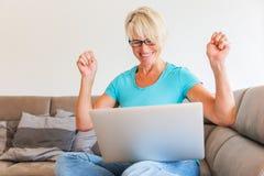 成熟妇女坐在膝上型计算机前面的欣喜 库存图片