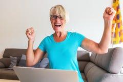 成熟妇女坐在膝上型计算机前面的欣喜 免版税库存照片