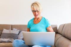 成熟妇女坐谁高兴用在膝上型计算机前面的被举的手 免版税库存照片