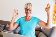 成熟妇女坐谁高兴用在膝上型计算机前面的被举的手 库存照片