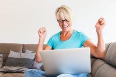成熟妇女坐谁高兴用在膝上型计算机前面的被举的手 图库摄影
