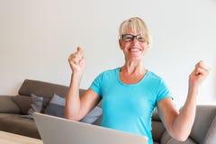 成熟妇女坐谁高兴用在膝上型计算机前面的被举的手 免版税图库摄影