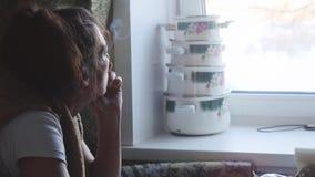 成熟妇女抽一根电子香烟反对窗口 光美妙地阐明的烟后面 免版税库存照片