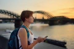 成熟妇女敬佩科隆,德国令人惊讶的日落视图  免版税库存照片