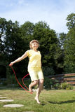 成熟妇女有乐趣跳绳 免版税库存图片