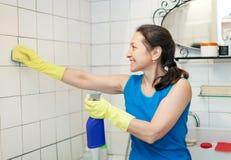 成熟妇女清洗铺磁砖的墙壁 免版税图库摄影