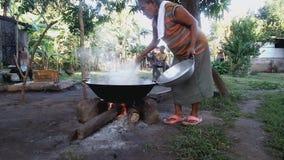 成熟妇女烹调室外使用巨大的平底锅和木柴 影视素材