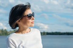 成熟妇女画象外形的在基于自然的太阳镜在河附近 免版税库存照片