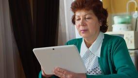 成熟妇女画象有一台白色片剂个人计算机的在家 库存照片